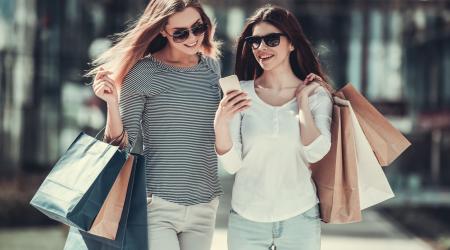 Deux femmes font du shopping et regardent un téléphone portable
