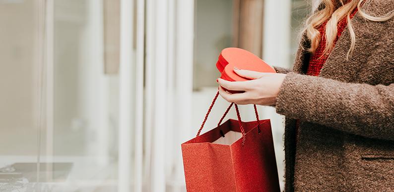 femme avec un sac rouge faisant du shopping pour la saint valentin