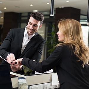 Le client présente sa carte de fidélité à la réception de l'hôtel