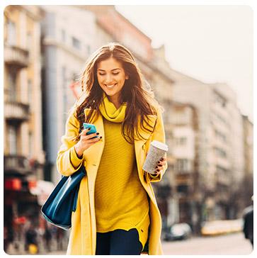 Femme dans la rue avec un café tenant son téléphone portable
